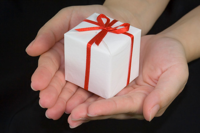 A gift being given in a pair of outreaching hands.